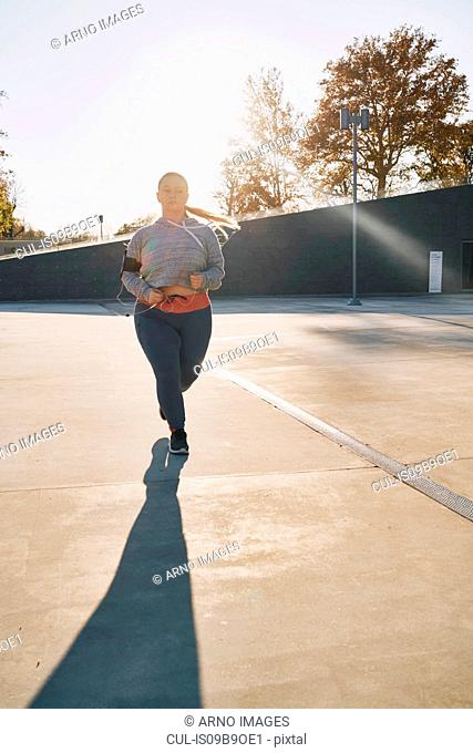 Curvaceous young female runner running in sunlight