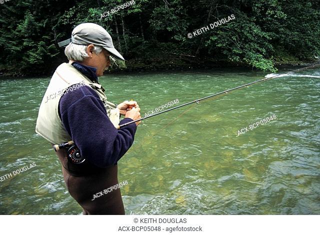 Flyfisherman tying on fly, Dean river, British Columbia, Canada