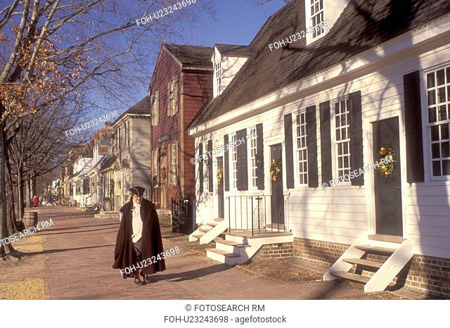 Colonial Williamsburg, Virginia, VA, Williamsburg, A man interpreter wearing a colonial costume walks down the sidewalk outside the village stores in Colonial...