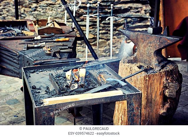 Blacksmiths working process on metal at forge