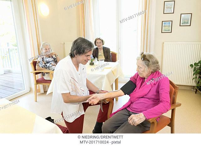 Caretaker checking blood pressure of senior woman in rest home