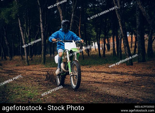 Male teenage boy riding motorcycle on dirt road in forest