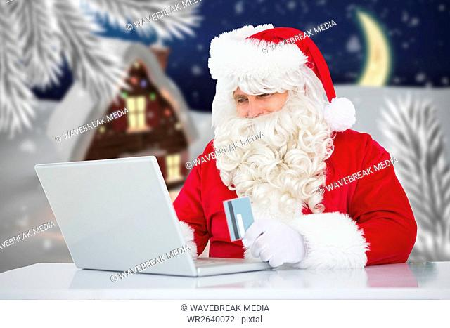 Santa claus doing online shopping with credit card on laptop
