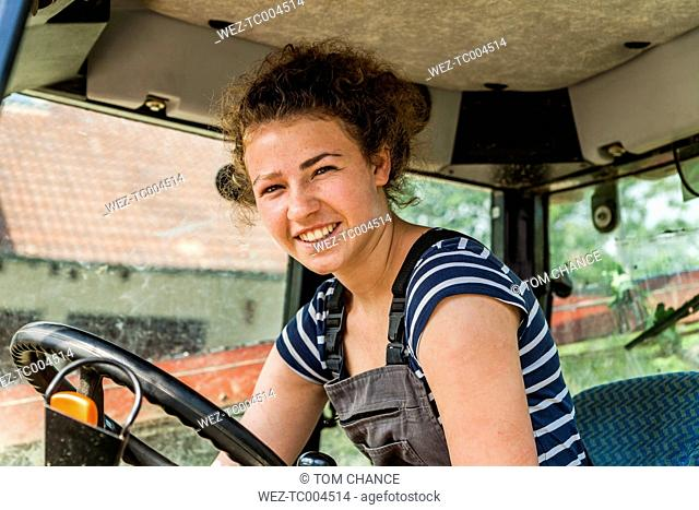Portrait of smiling farmwoman in tractor