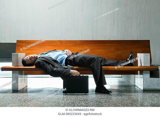 Side profile of a businessman sleeping on a bench