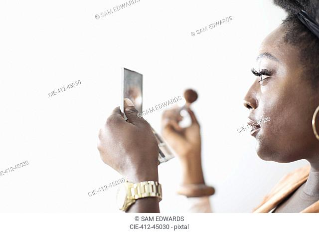 Woman applying makeup in compact mirror