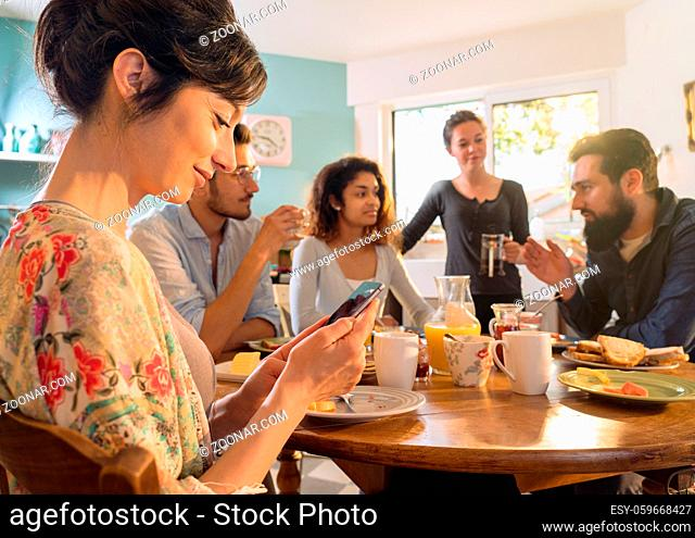 A group of multi-ethnic friends gathered around a table in the kitchen for breakfast. in the foreground a young woman looks at her messages on her phone