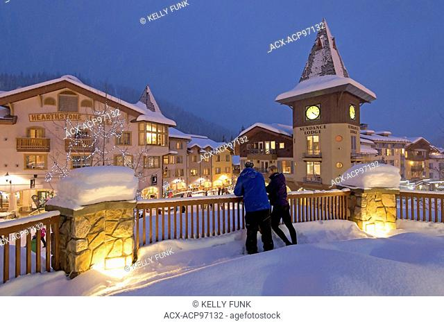 A young couple enjoys a snowy evening in the village of Sun Peaks, Thompson Okangan region, British Columbia, Canada