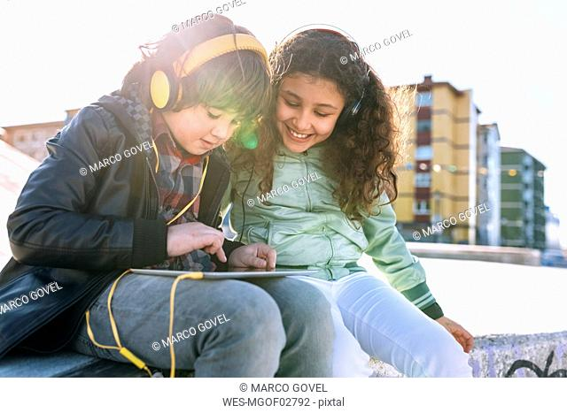 Two children with headphones and tablet