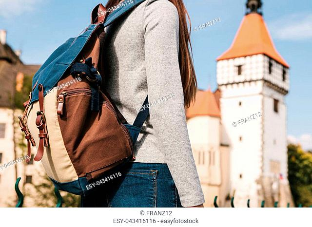 A tourist with a backpack looks at the sights. The castle called Blatna in the Czech Republic is blurred in the background. Holidays, travel
