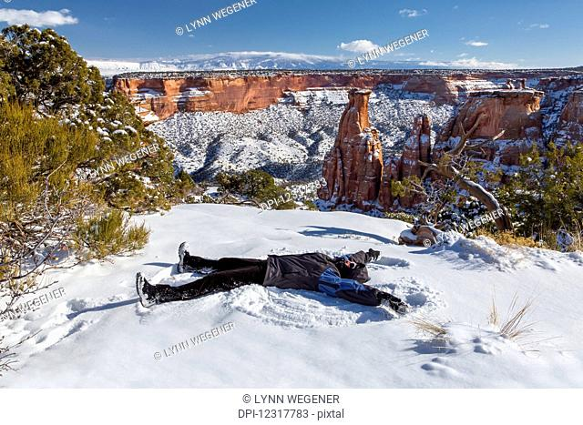 A woman makes a snow angel in the snow in front of the 450 foot high sandstone Independence Monument in the Colorado National Monument; Colorado