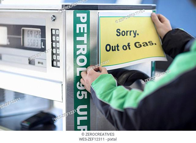Petrol attendant attaching out of gas sign