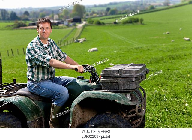 Portrait of farmer riding tractor in field with sheep
