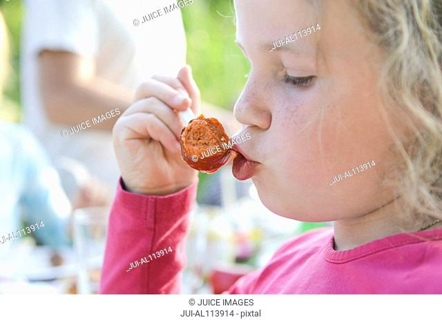 Young girl eating sausage