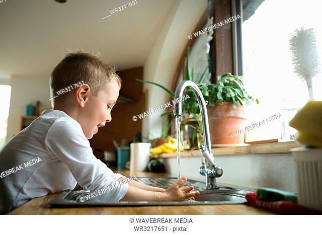 Boy washing hands on kitchen sink