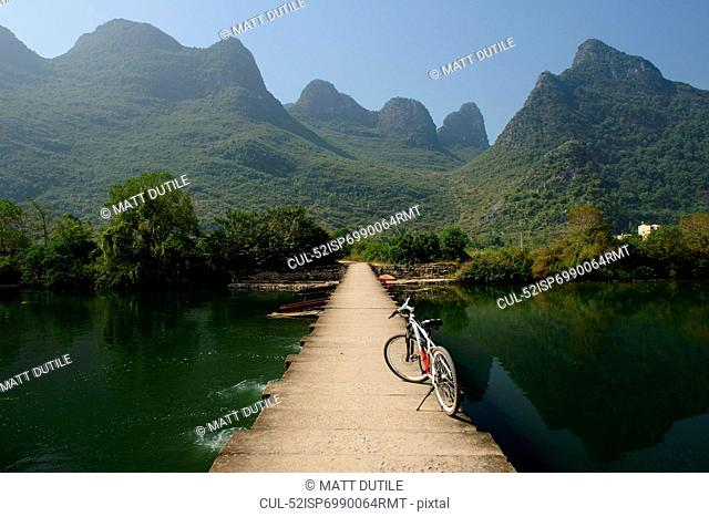 Bicycle on wooden dock in lake