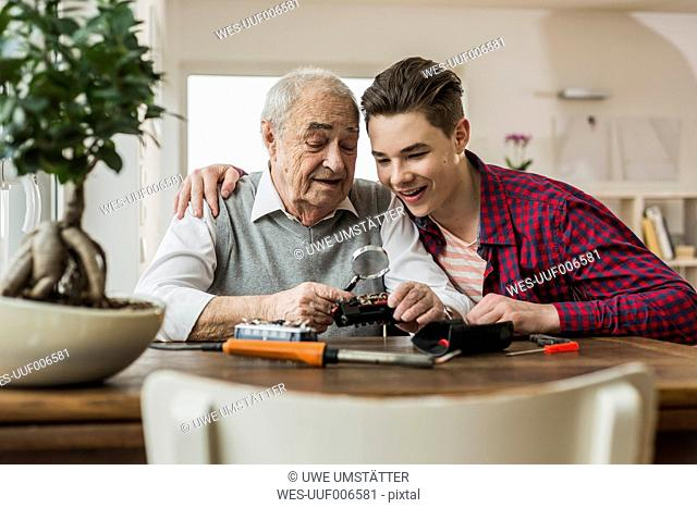 Portrait of senior man and grandson with toy train at home
