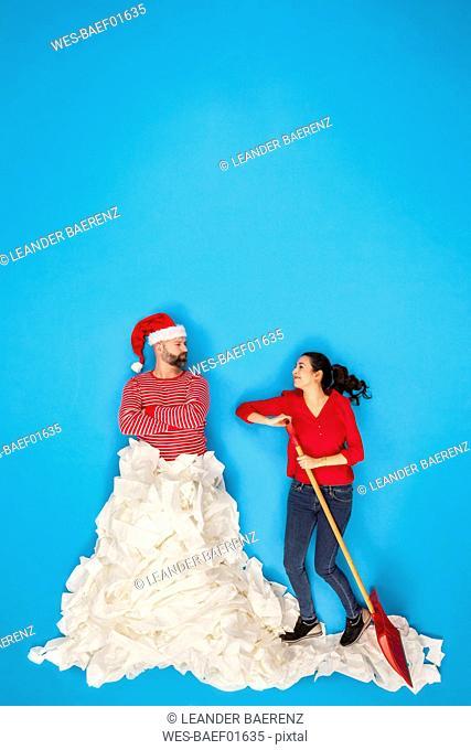 Couple shoveling snow, man wearing Santa hat