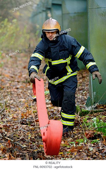 A fireman is rolling out a tube