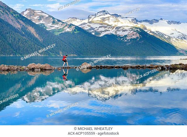 Woman navigates rock stepping stones at Garibaldi Lake, Garibaldi Provincial Park, British Columbia, Canada