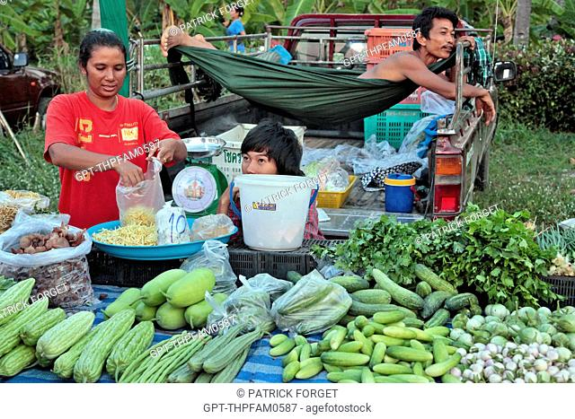 THE MAN RELAXING AND THE WOMAN WORKING, VEGETABLE STALL, EVENING MARKET, BANG SAPHAN, THAILAND, ASIA