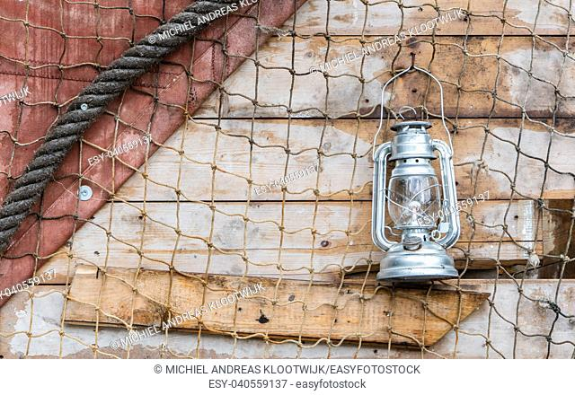 Old kerosene lamp hanging on the wall of a wooden house