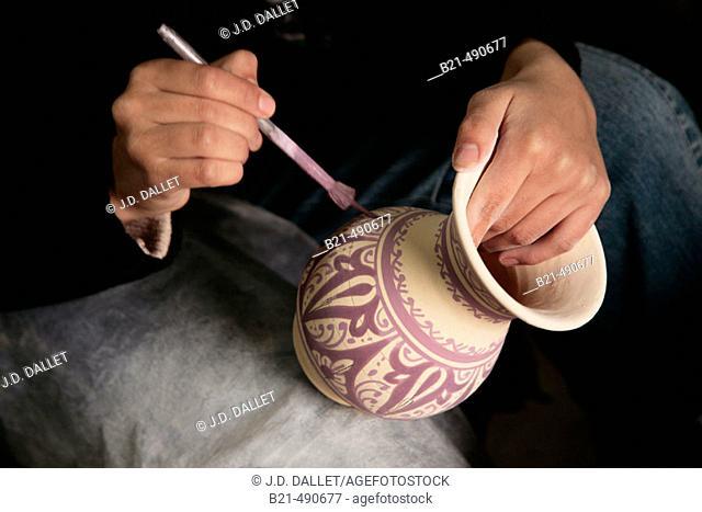 Painting typical Fes ceramic, at 'Serghini-Poterie de Fes', at Aïn Nokbi, outside Fes. Morocco