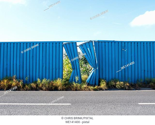 Two blue fence panels damaged on the side of a road in Cheshire, UK