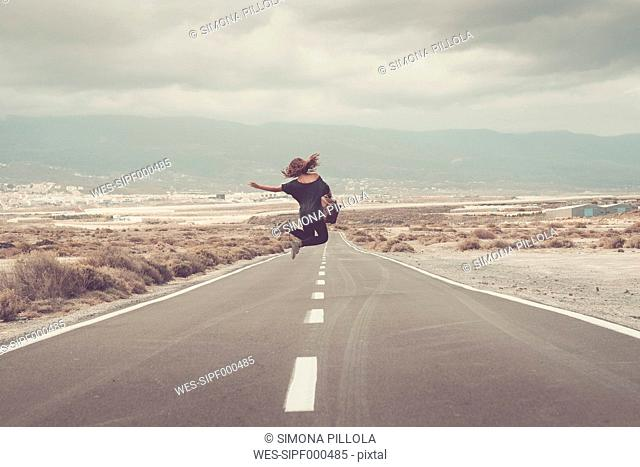 Young woman jumping for joy on a road