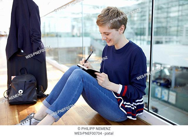 Blond businesswoman sitting on ground, writing in notebook