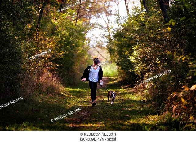 Young girl walking dog in rural setting