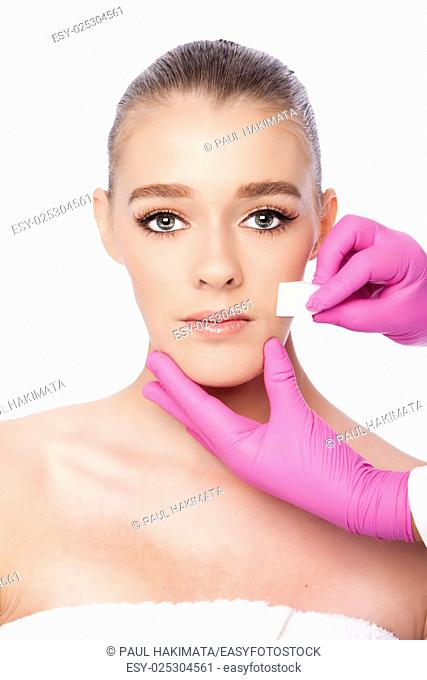 Beautiful face cleansing Cosmetic skincare spa beauty treatment with pink gloves and sponge, on white