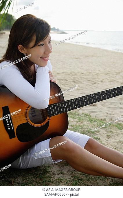 Young woman sitting on beach, leaning on guitar