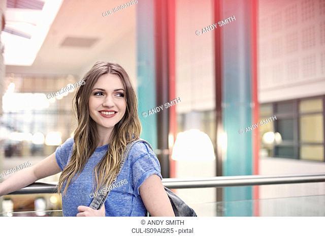 Young woman wearing blue t shirt looking away