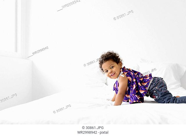 Young girl with curly black hair crawling on a bed, wearing jeans and printed top, smiling at camera