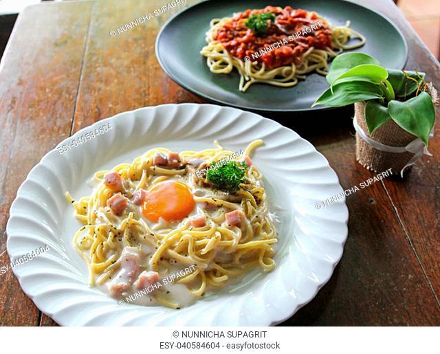 Spaghetti Carbonara with egg yolk and Spaghetti italian pasta with tomato sauce on wooden table