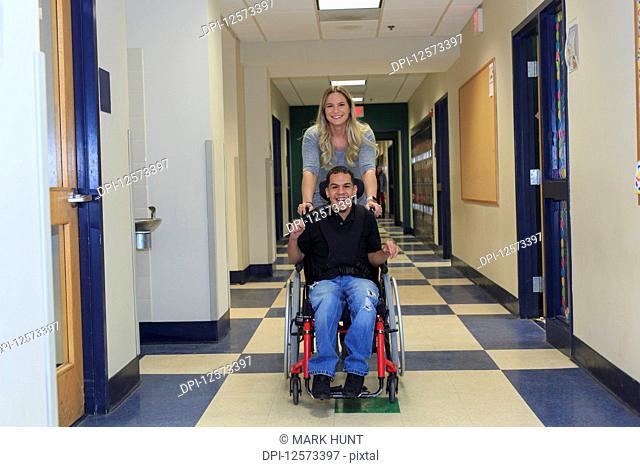 Boy with Spastic Quadriplegic Cerebral Palsy and teacher in the school hallway