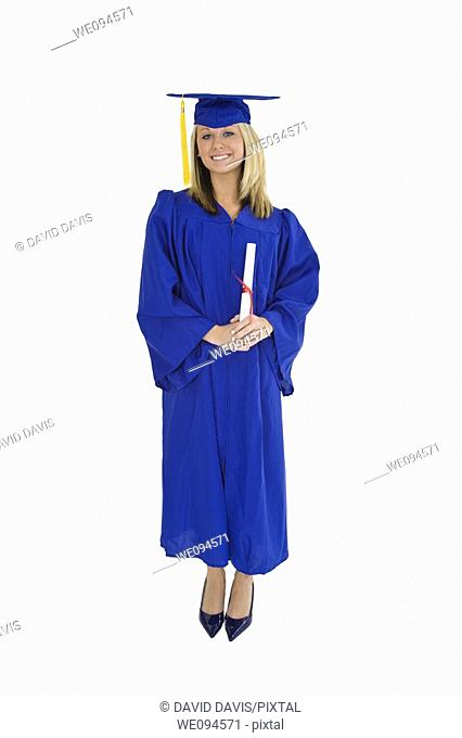 A female caucasian with blond hair standing in blue graduation gown and smiling  She is on a white background