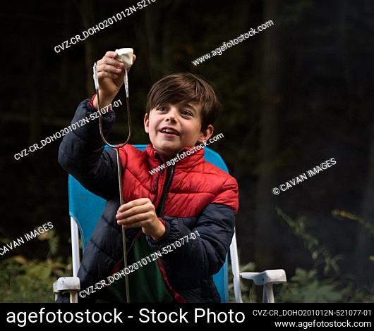 Boy taking a roasted marshmallow off of a metal stick outdoors