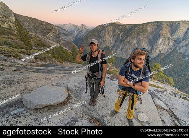 Two hikers at the top of El Capitan in Yosemite Valley at sunset