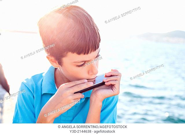 Young Boy Playing the Harmonica