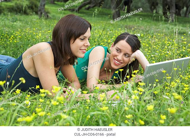 Two young women lying in meadow with laptop