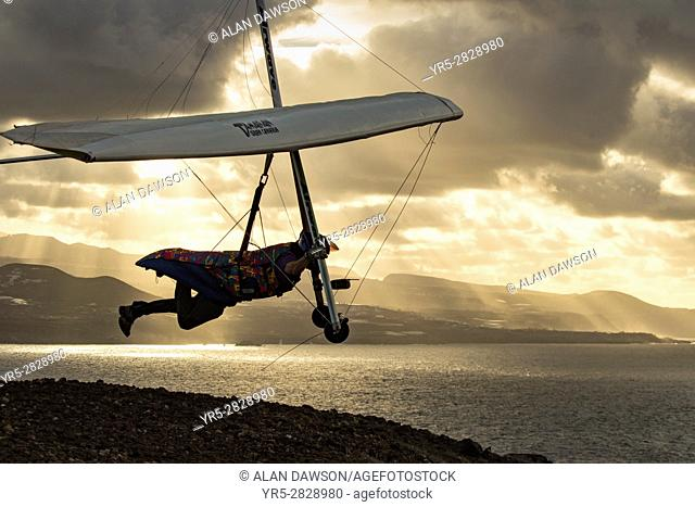 Las Palams, Gran Canaria, Canary Islands, Spain. Hang glider taking off from cliff overlooking Atlantic Ocean shortly before sunset near Las Palmas on the north...