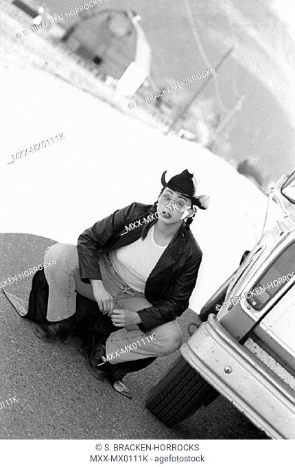 Young woman crouching by truck