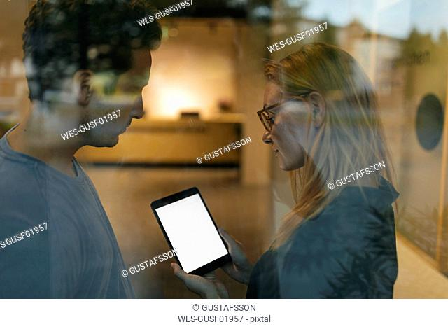 Young man and woman sharing tablet behind windowpane