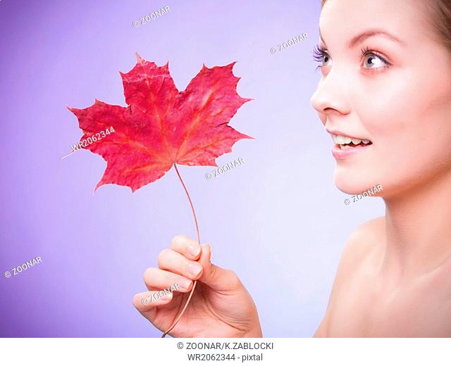 Skin care. Portrait of young woman girl with red maple leaf