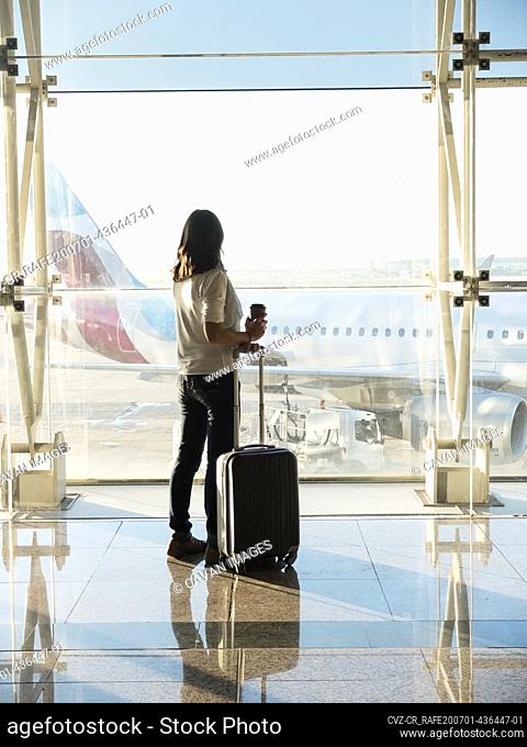 Young woman standing with baggage near the airport window waiting for the flight