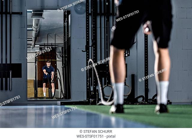 Athletic young man exercising with battle ropes at gym