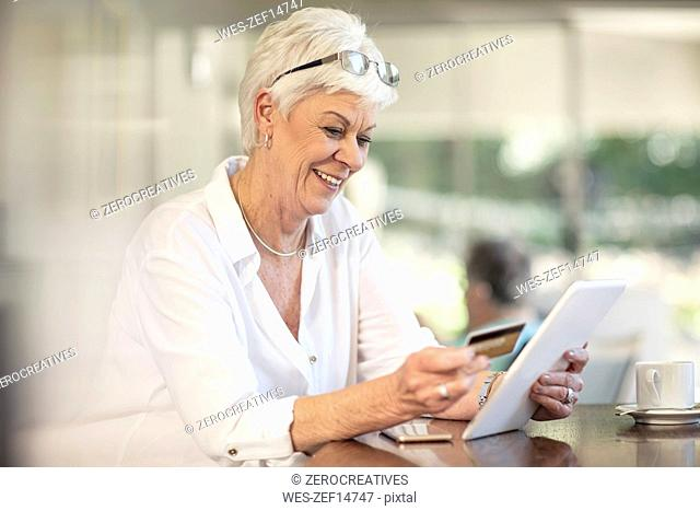 Senior woman shopping online with credit card