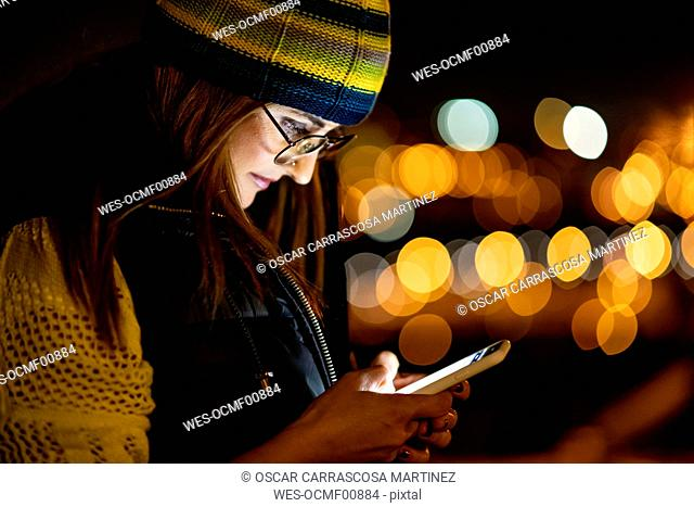 Young woman using smartphone, wearing hat at night